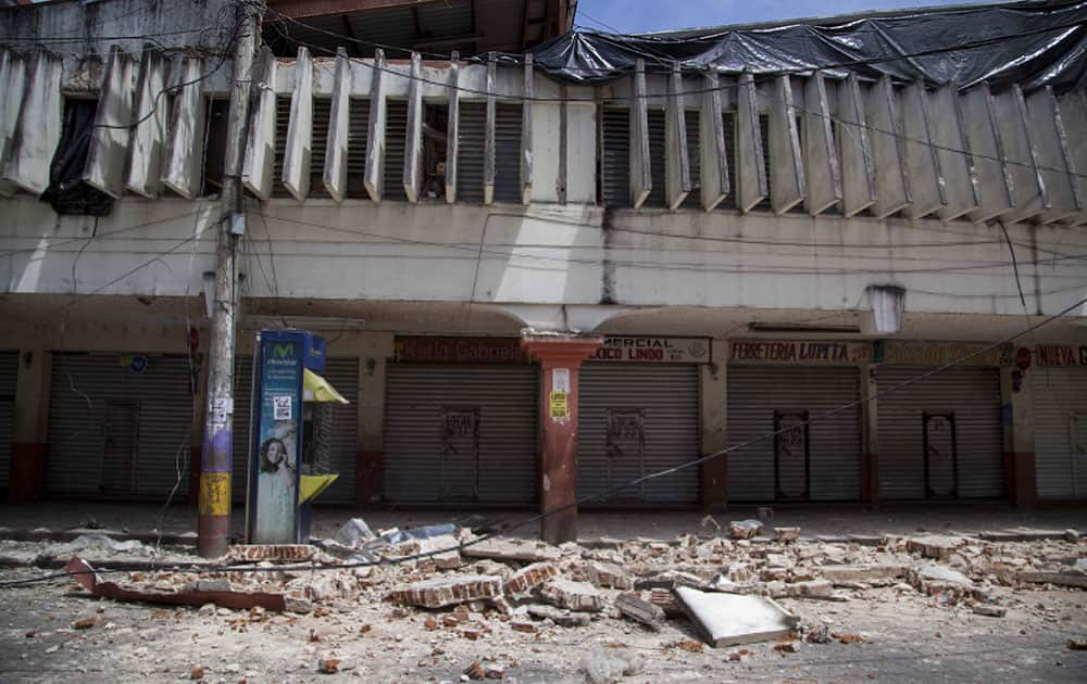 Wreckage and debris from buildings damaged by an earthquake lie on the street of San Pedro, Guatemala, Monday, July 7, 2014. An earthquake measuring 6.9 on the Pacific Coast shook a wide area of southern Mexico and Central America Monday.