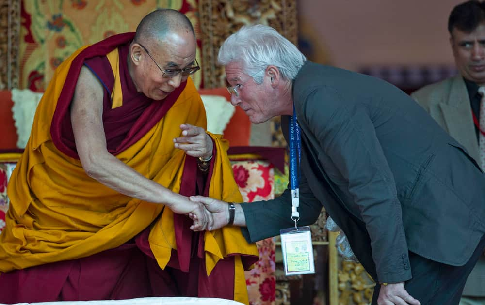Tibetan spiritual leader the Dalai Lama shakes hand with hollywood actor Richard Gere, right, before teachings on the fourth day of Kalachakra near Leh, India.