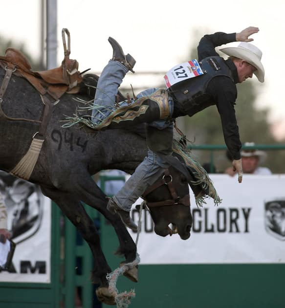 Jacobs Crawley of Stephenville, Texas, comes off the horse in the saddle bronco riding event at Reno Rodeo in Reno.