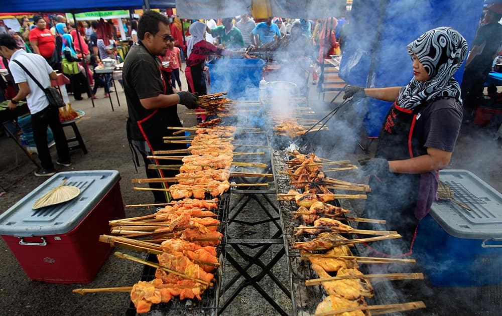 Muslim vendors prepare local dish Ayam Percik for sale at a Ramadan bazaar in Shah Alam, outside Kuala Lumpur, Malaysia.