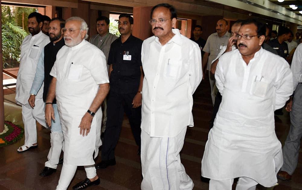Prime Minister Narendra Modi flanked by Union Minister for Parliamentary Affairs M Venkaiah Naidu and MoS Prakash Javadekar at Parliament House in New Delhi.