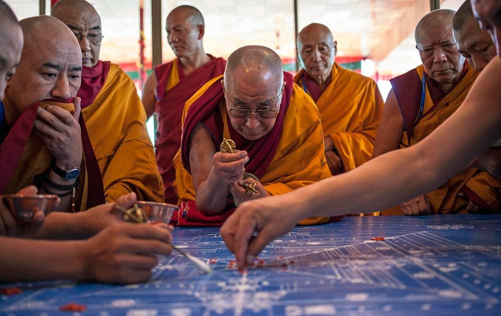 Tibetan spiritual leader the Dalai Lama concentrates during the preparation of a Sand Mandala, a spiritual and ritual symbol depicting the Buddhist universe, during third day of Kalachakra near Leh.