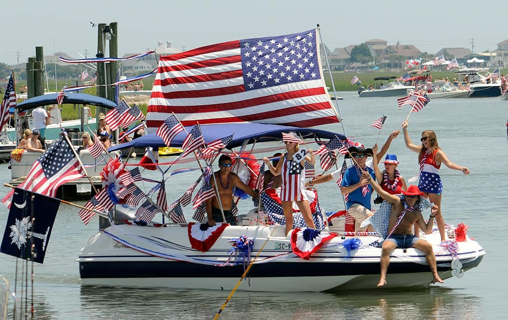 People wave from a boat adorned with bunting and US flags during the 31st annual Murrells Inlet Fourth of July Boat Parade.