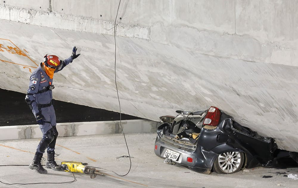 A policeman looks at a car crushed underneath a collapsed bridge in Belo Horizonte, Brazil.