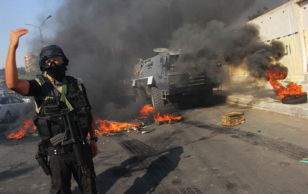 An Egyptian security forces member directs others during clashes against supporters of ousted President Mohammed Morsi in Cairo`s Suez Bridge district, Egypt.