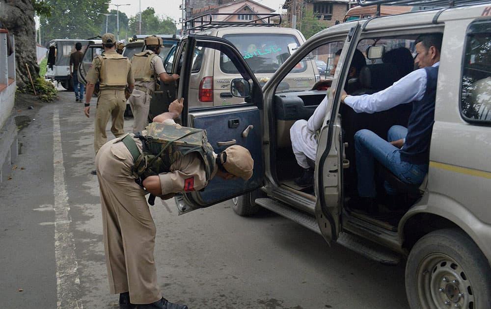 Policemen check vehicles in Srinagar.