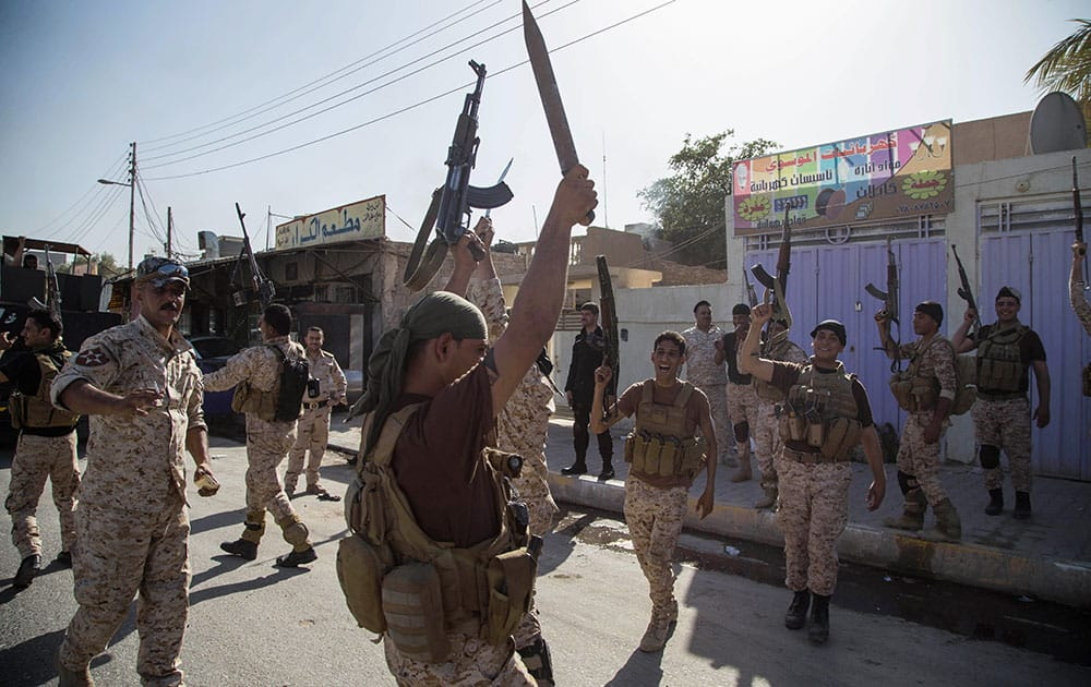 Iraqi security forces celebrate after clashes with followers of Shiite cleric Mahmoud al-Sarkhi, in front of his home in the Shiite holy city of Karbala.