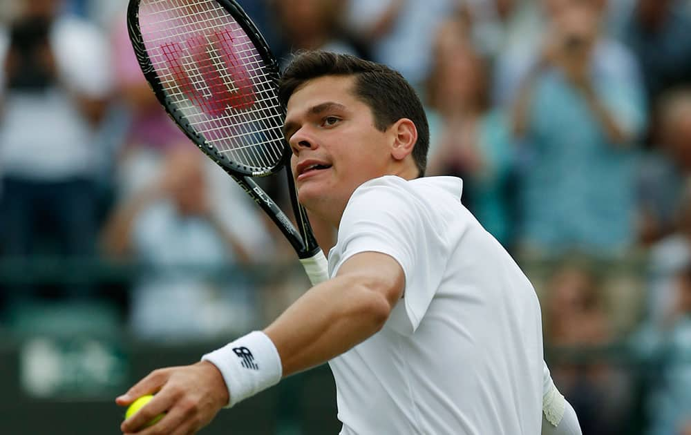 Milos Raonic of Canada tosses the ball to the crowd after defeating Nick Kyrgios of Australia in their men`s singles quarterfinal match at the All England Lawn Tennis Championships in Wimbledon.
