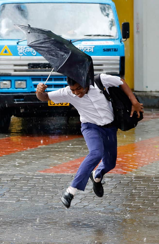 A school boy jumps over a puddle of water as it rains in Mumbai.