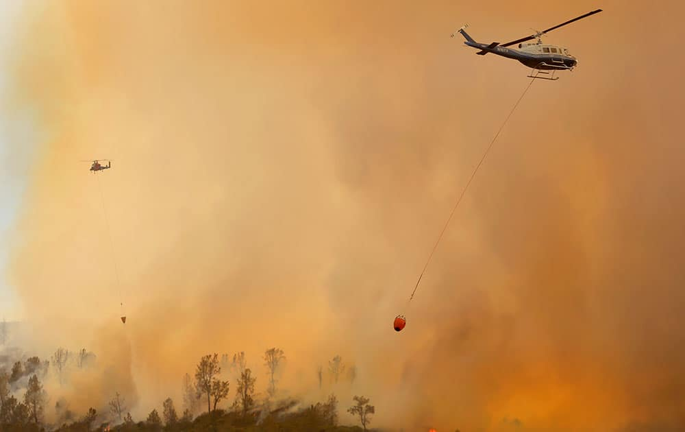 Private hire helicopters make water drops on the Butts Fire above Snell Valley as the afternoon winds kicked up, near Middletown, Calif.