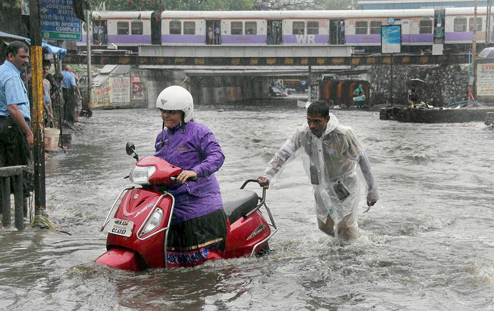 A vehicle moves through a water logged street as the city experienced heavy rainfall in Mumbai.