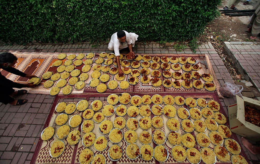 A Pakistani arranges plates of food prepared and ready for free distribution for the Iftar meal that breaks the day`s fast at sunset, during the Islamic holy month of Ramadan outside a mosque in Islamabad.