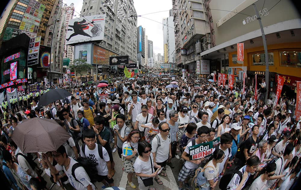 People fill in a street during a march at an annual protest in downtown Hong Kong. ens of thousands of Hong Kong residents marched through the streets of the former British colony to push for greater democracy in a rally fueled by anger over Beijing`s recent warning that it holds the ultimate authority over the southern Chinese financial center.