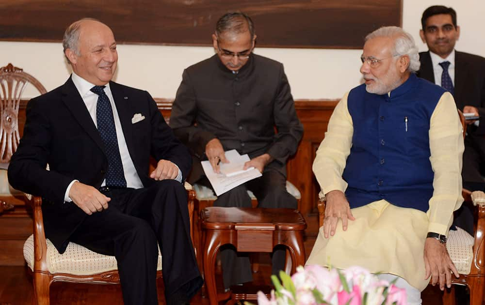 French Foreign Minister Laurent Fabius, left, talks with Indian Prime Minister Narendra Modi during their meeting at his residence in New Delhi. Fabius is in India for a two-day official visit.