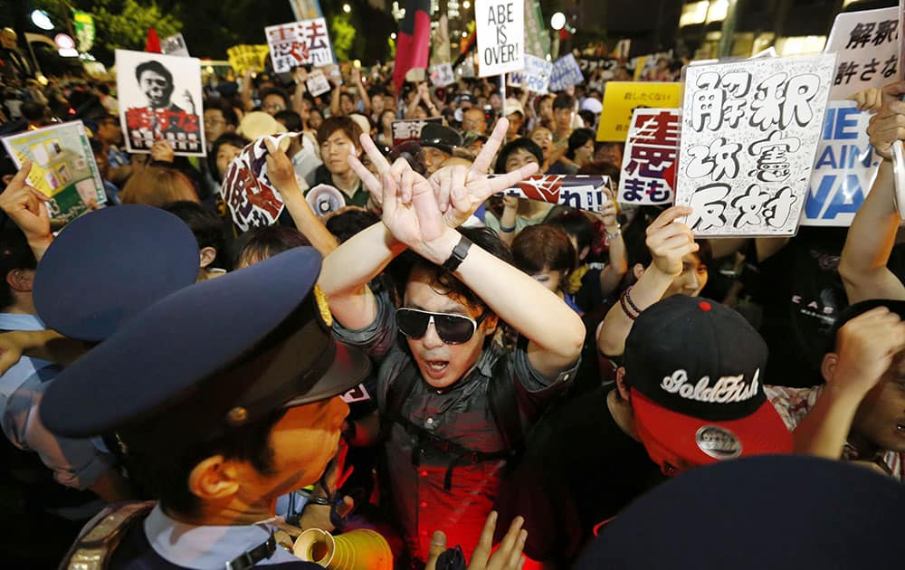 Protesters are blocked by police officers during a rally outside Prime Minister Shinzo Abe's official residence in Tokyo.