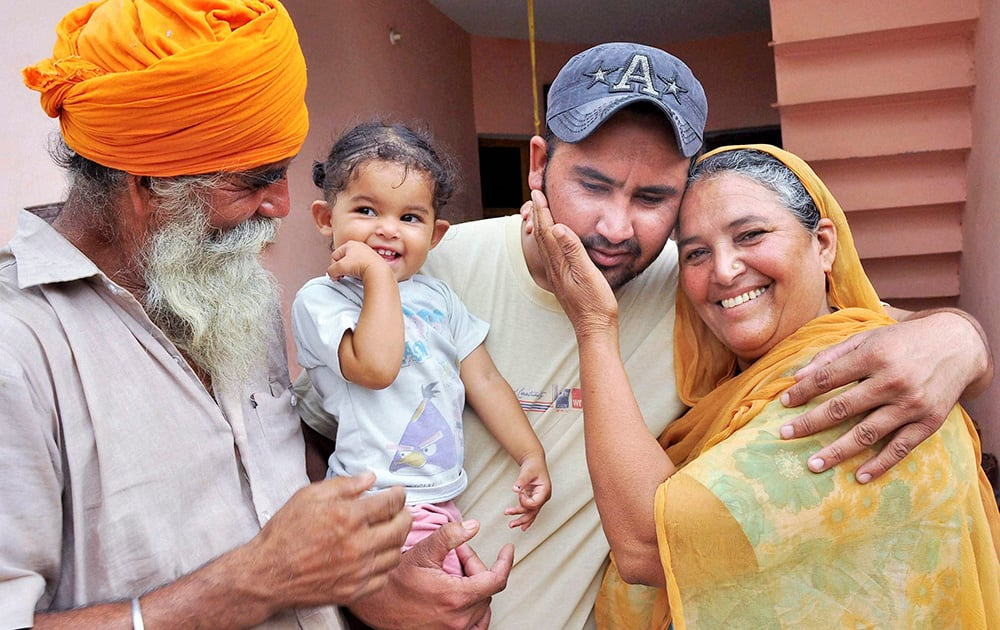Harjinder Singh who returned from Iraq, with his family members in Khatoli village in Patiala.