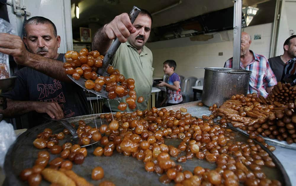 Palestinian vendors sells fried dough ball sweets locally called `awwamaat` at a shop on the first day of the Muslim holy month of Ramadan in the West Bank city of Nablus