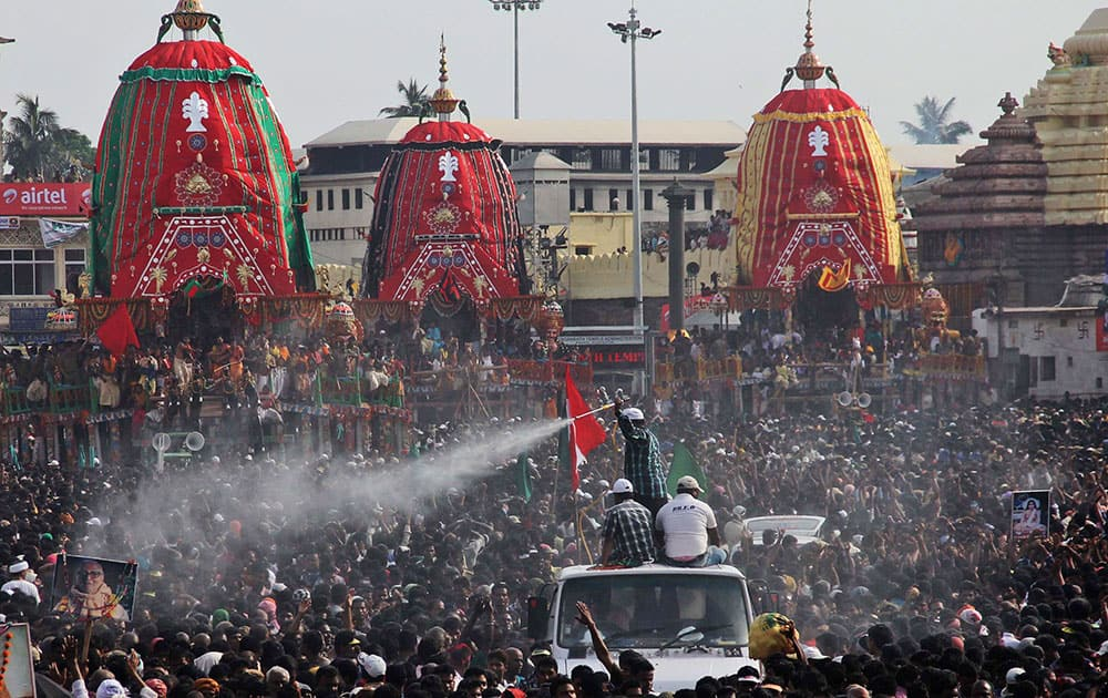 Volunteers spray water on devotees to cool them during the annual Hindu festival 'Rath Yatra' or chariot procession in Puri, Orissa state.