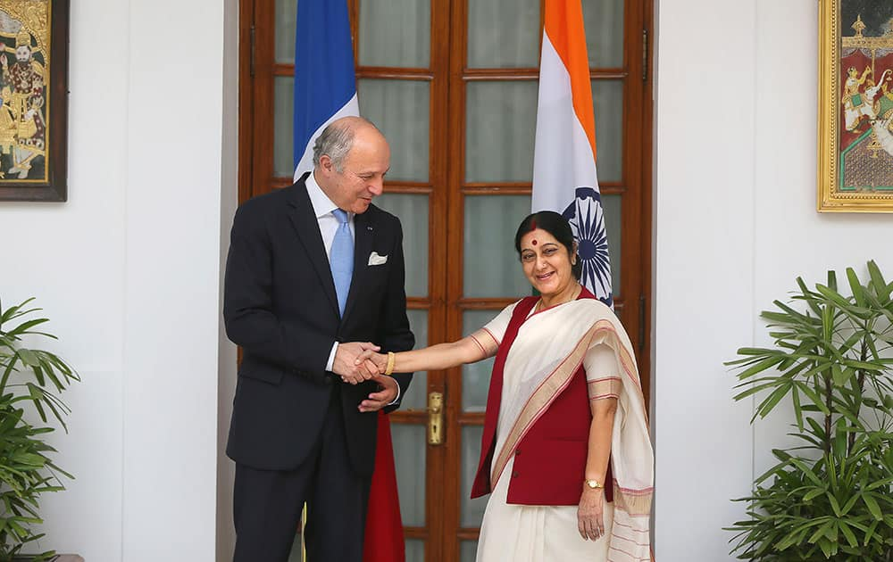 Foreign Minister Sushma Swaraj, right, shakes hand with her French counterpart Laurent Fabius in New Delhi.