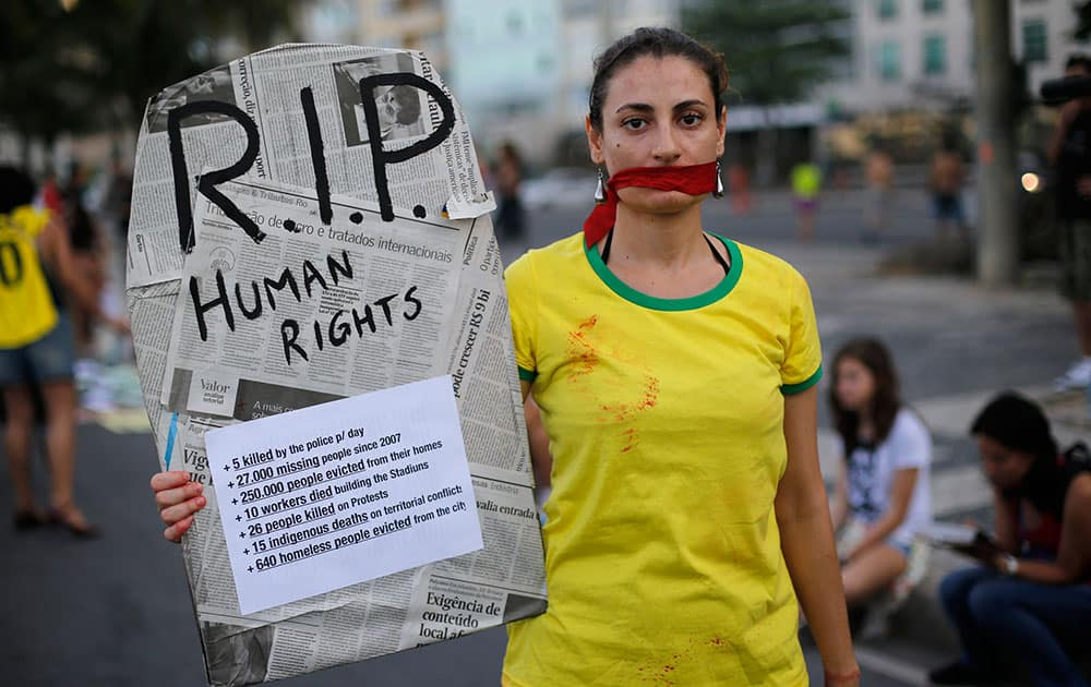 A woman wears a t-shirt with the Brazil national colors while holding a sign with the form of a coffin that reads, `R.I.P Human Rights` during a protest against the money spent on the 2014 soccer World Cup and demanding better public services, at Copacabana beach in Rio de Janeiro, Brazil.