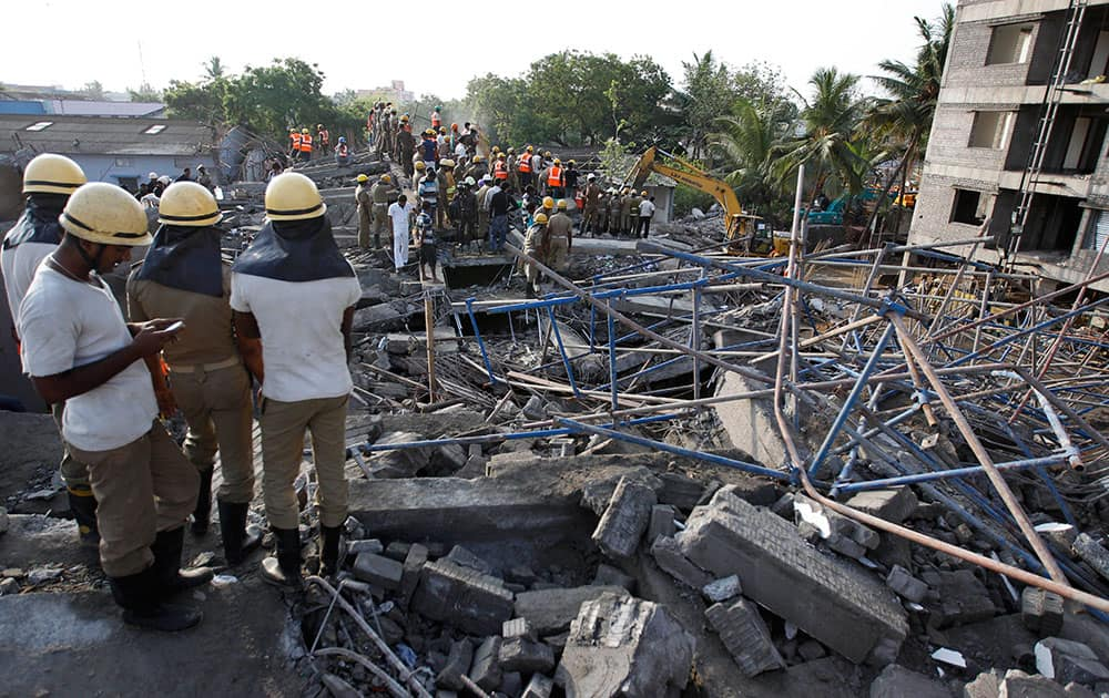 A rescuer, left checks his mobile phone as they search amid the rubble of a building that collapsed late Saturday during monsoon rains on the outskirts of Chennai, India. Police said dozens of workers have been pulled out so far and the search is continuing.