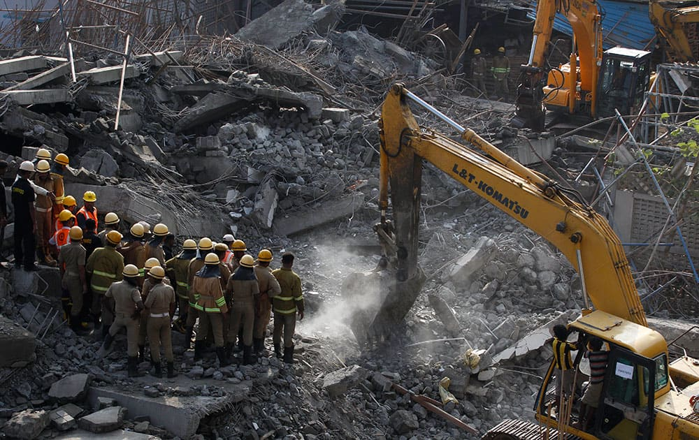 Rescuers search amid the rubble of a building that collapsed on the outskirts of Chennai, India.