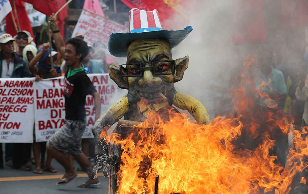 A Filipino activist runs beside a burning effigy of Philippine President Benigno Aquino III as they try to get near his house a day before the Comprehensive Agrarian Reform program expires in suburban Quezon city, north of Manila, Philippines.