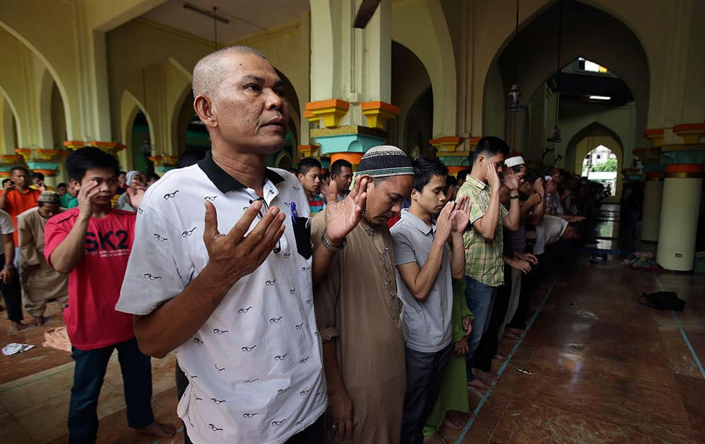 Filipino Muslims gesture as they pray during the first day of the holy fasting month of Ramadan at the Golden Mosque in downtown Manila, Philippines.