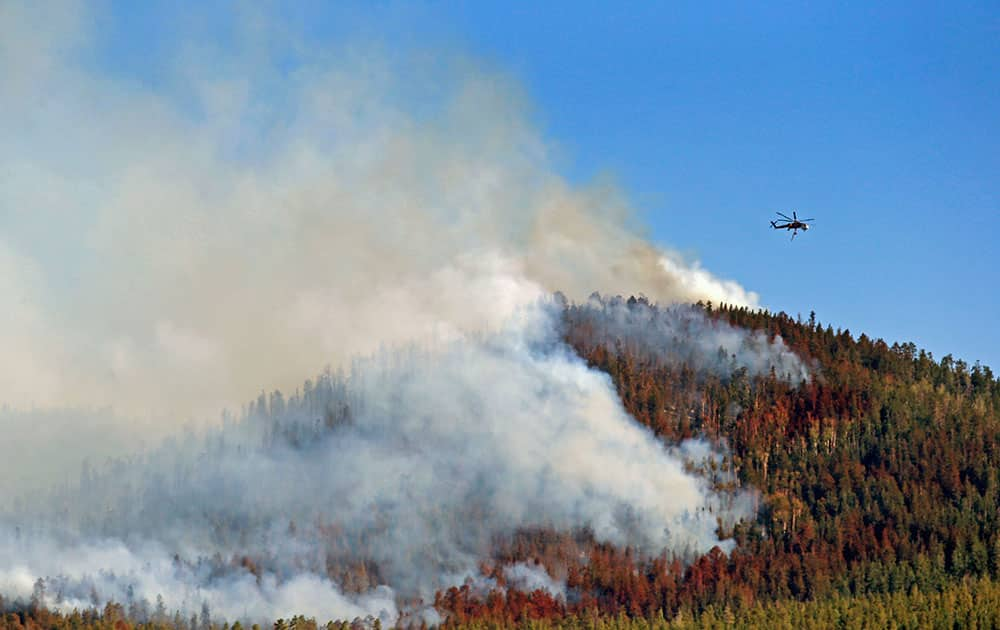 A helicopter hovers above the San Juan Fire, in Vernon, Ariz. Emergency crews have set up a shelter for evacuees of a wildfire in northeastern Arizona`s White Mountains that has charred more than 8 square miles.