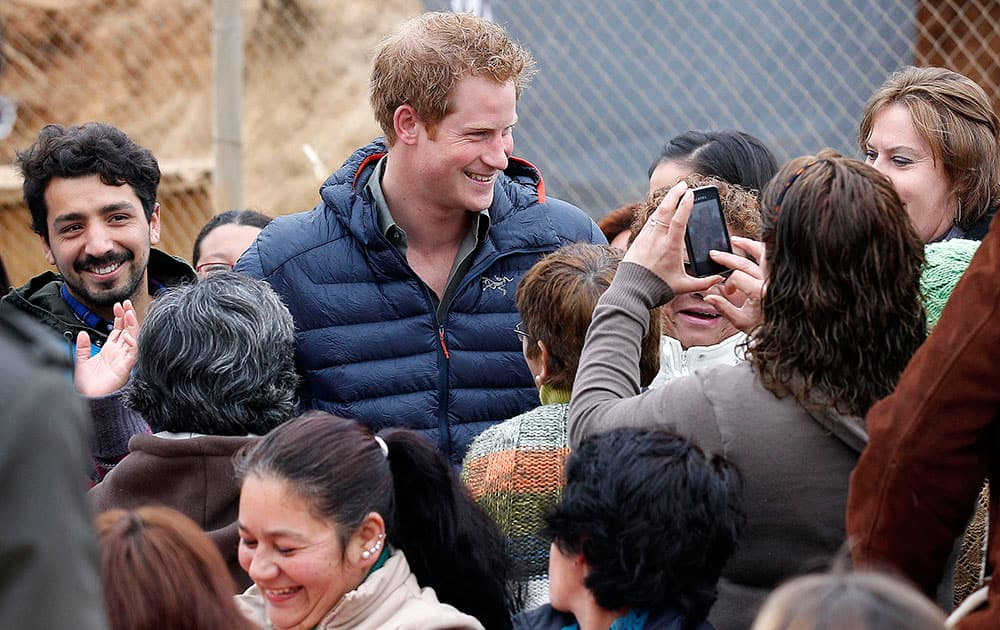 Britain`s Prince Harry poses for pictures as he visits families living in temporary housing in the El Vergel slum after they lost their homes to an April forest fire in Valparaiso, Chile.