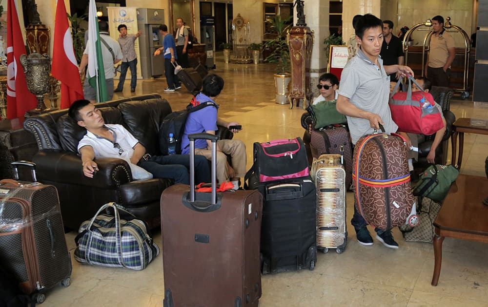 Chinese workers who fled from Samarra, Iraq, wait for buses to begin their journey home as they sit at a hotel in Baghdad, Iraq.