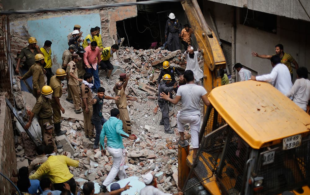 Rescuers gesture for an excavator to stop as they try to retrieve the body of a victim at the site of a building collapse in New Delhi.