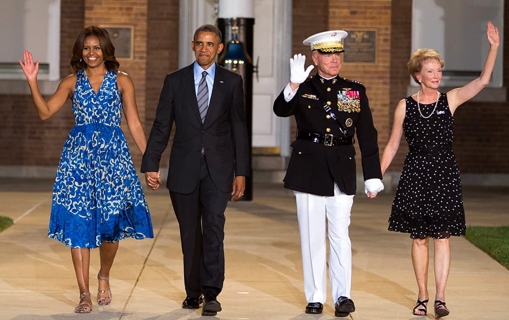 President Barack Obama and first lady Michelle Obama are escorted to their seats by Marine Commandant Gen. James Amos and his wife Bonnie Amos during the Marine Barracks Evening Parade in Washington.