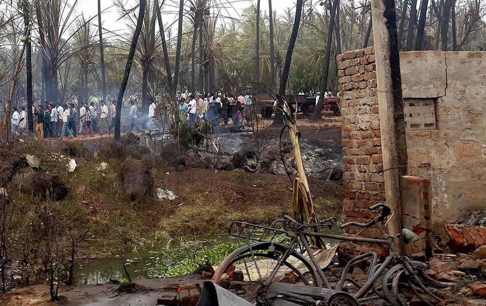 People standing near coconut trees burnt in GAIL gas leak fire in Nagaram village near Rajahmundry in East Godavari district of Andhra.