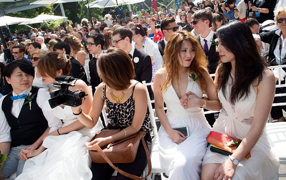 Cindy Su, second from left, holds the hand of her wife Lana Yu who flew from Taiwan to join over 100 gay couples in a mass wedding during World Pride 2014 at Casa Loma in Toronto.