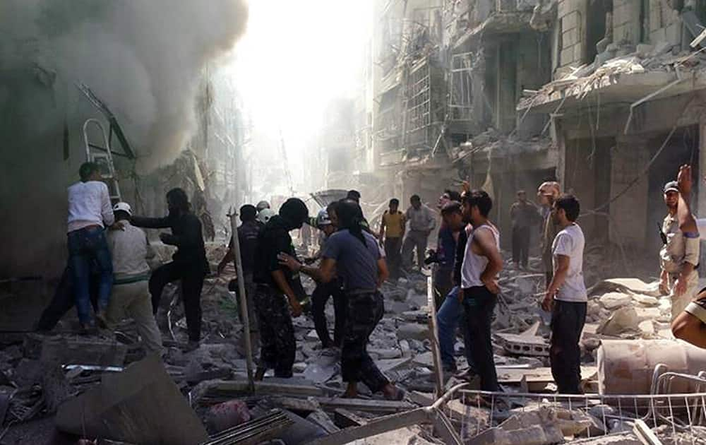 This photo provided by the anti-government activist group Syrian Observatory for Human Rights, which has been authenticated based on its contents and other AP reporting, shows Syrians inspect an area amid the rubble of destroyed buildings following a Syrian government airstrike at Karm al-Jabal area in Aleppo, Syria.