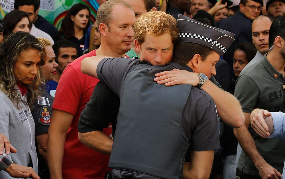 Britain`s Prince Harry hugs a police officer as he finishes his visit to a social project that aims to reduce drug addiction in an area known as `Crackland` in Sao Paulo, Brazil.