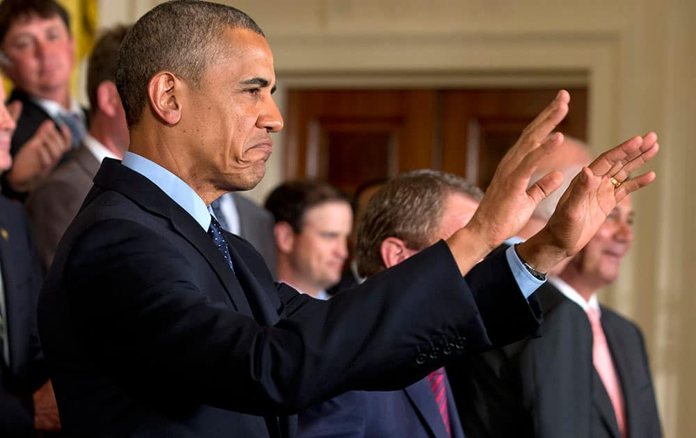 President Barack Obama gestures for the crowd to sit down before speaking at a ceremony honoring the 2013 Presidents Cup U.S. team during a ceremony in the East Room of the White House.