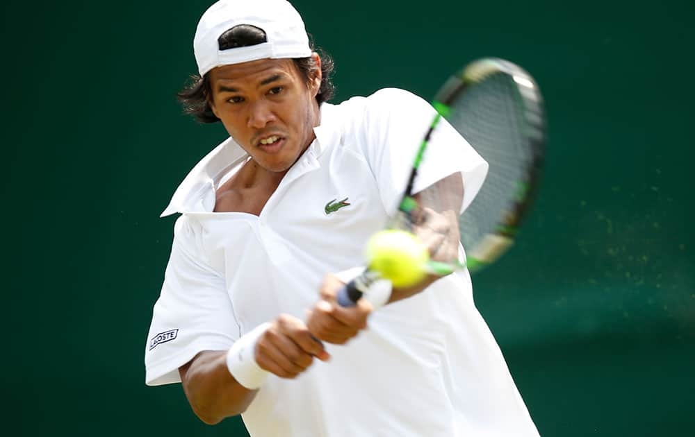 Somdev Devvarman of India plays a return to Jerzy Janowicz of Poland during their first round match at the All England Lawn Tennis Championships in Wimbledon, London.