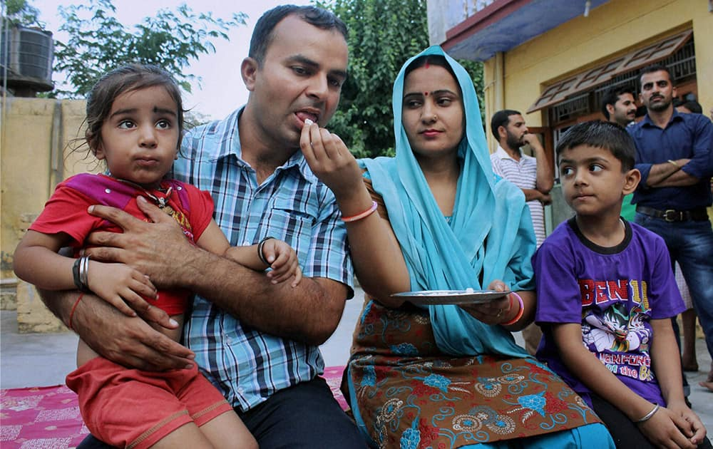 Indian construction worker Rajesh Kumar, one of 40 Indian workers abducted in the Iraqi city of Mosul by militants, with his families at Miran Sahib in Jammu.