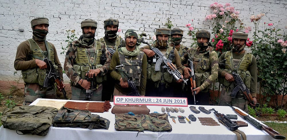 Army personnel display arms and ammunition recovered from Lashkir-e-Toiba (LeT) hideout during an anti-militant operation at Rajwara Forests in Kupwara.