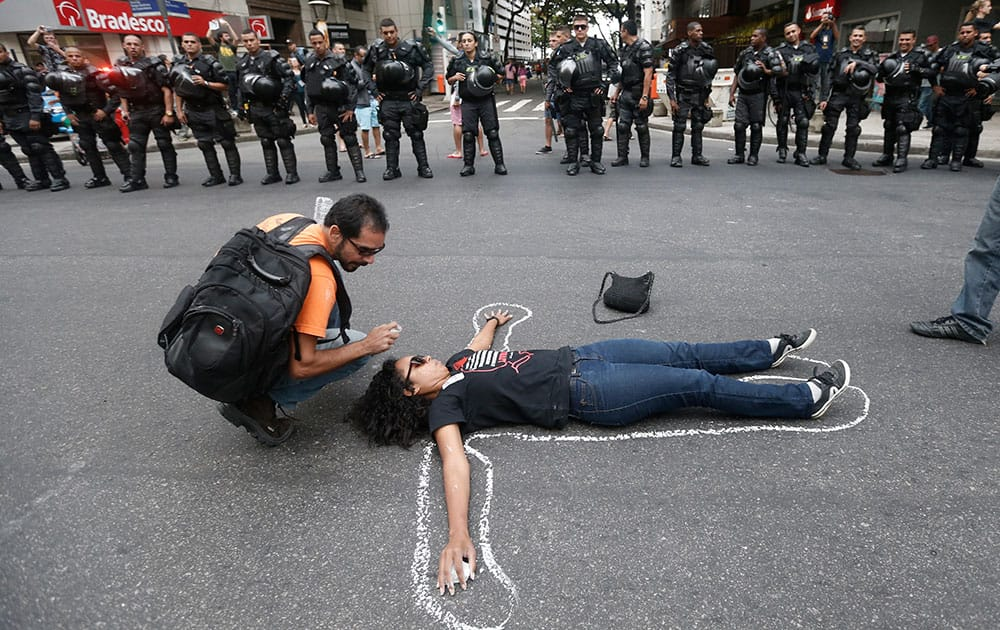 A woman lays on the ground pretending to be a dead body in front of Brazil`s police during a protest against the money spent on the WCup 2014 and demanding better public services, in Rio de Janeiro, Brazil.