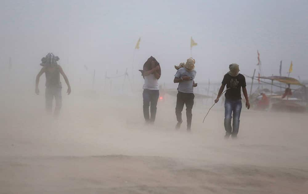 Indians walk during a dust storm on the banks of Sangam, the confluence of rivers the Ganges and the Yamuna in Allahabad.
