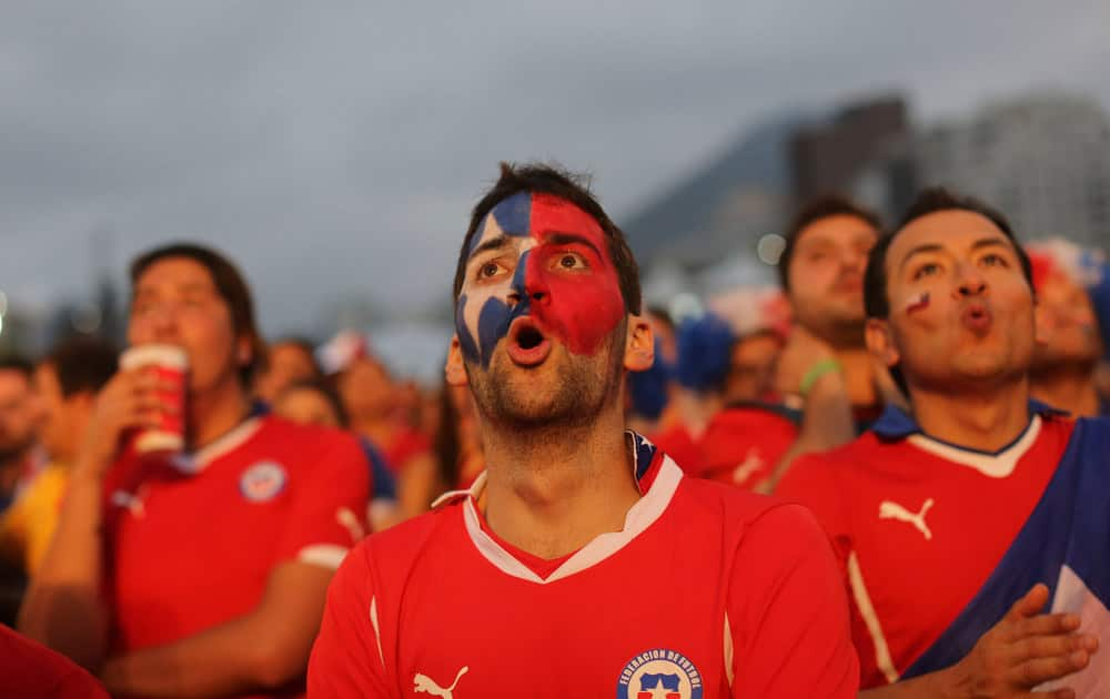 Soccer fans watch a live broadcast of the group B World Cup match between Chile and Spain, inside the FIFA Fan Fest area on Copacabana beach, in Rio de Janeiro, Brazil.