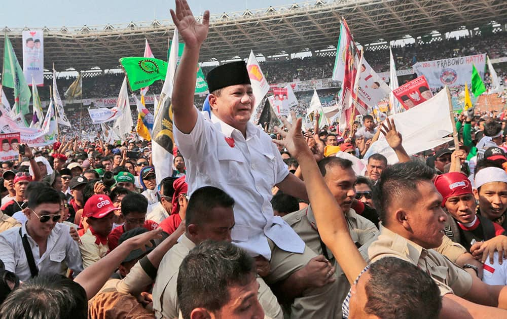 Indonesian presidential candidate Prabowo Subianto, center, is carried by his bodyguards as he greets his supporters during a campaign rally at Gelora Bung Karno Stadium in Jakarta, Indonesia.