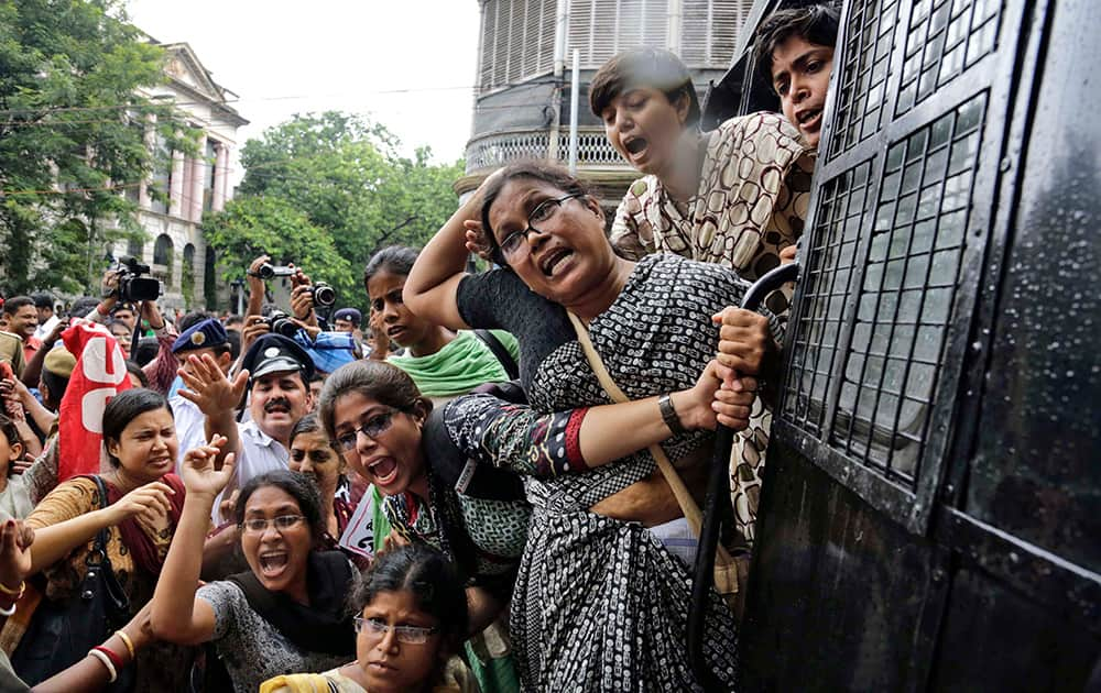 Activists of Socialist Unity Center of India (SUCI) shout slogans from a police van after being detained during a protest against hike in rail fare, outside the Governor`s house in Kolkata.