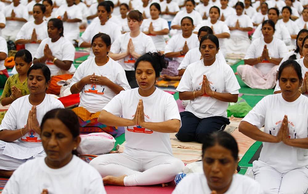 Yoga enthusiasts perform Surya Namaskar or sun salutation as they celebrate World Yoga Day in Bangalore.