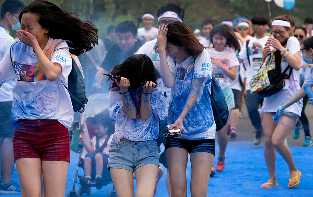 Participants try to cover themselves from color powder sprayed by volunteers as they run through a `color station` during a five-kilometer color run event held in Beijing, China.