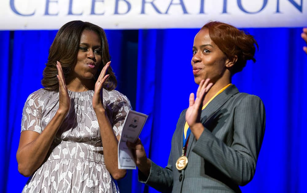 First lady Michelle Obama and graduate Jamila Lee mimic dancing as Lee is presented with a Student Achievement Award following Obama`s address at the DC College Access Program Class of 2014 graduation in Washington.
