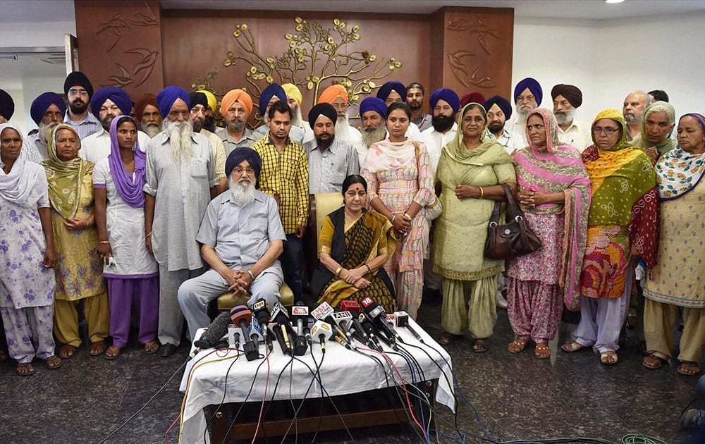External Affairs Minister Sushma Swaraj and Punjab Chief Minister Parkash Singh Badal with the families of some of the Punjabi workers abducted in Iraq, in New Delhi.